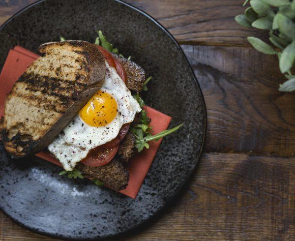 Crispy sujuk on sourdough dill mayo tomato fried egg
