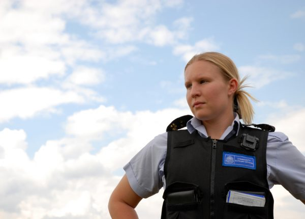 Police community support officer against a sky background.